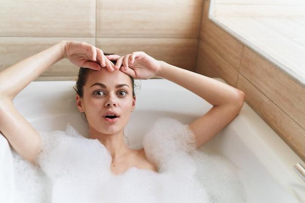 Красивая молодая женщина в своей красивой белоснежной ванне отдыхает и расслабляется, прекрасное свидетельство, ванна с пеной