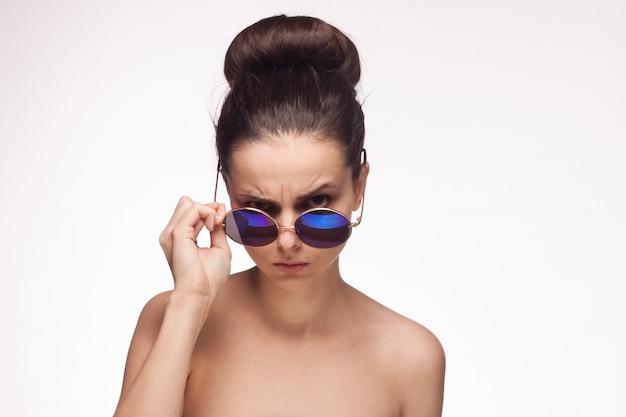 Молодая брюнетка женщина в очках, портрет на белой стене