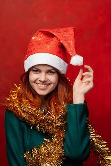 Веселая новогодняя женщина в шапке и мишуре, светлая стена