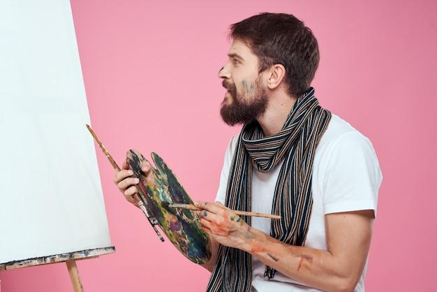 Мужской художник рисует картину на холсте мольбертом