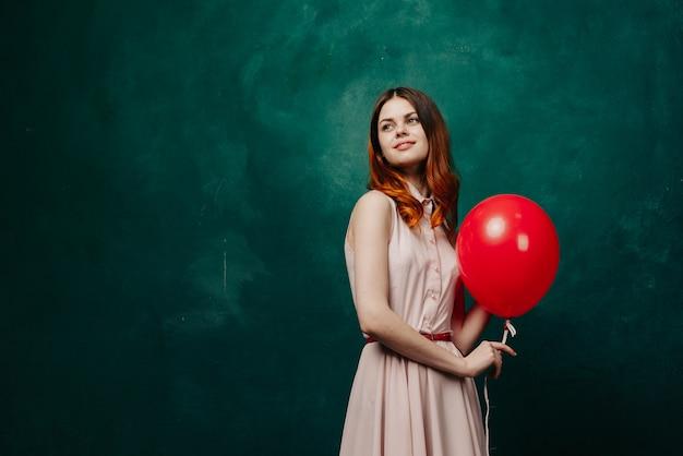 ドレス、スタジオで彼女の手で風船を持つ女性