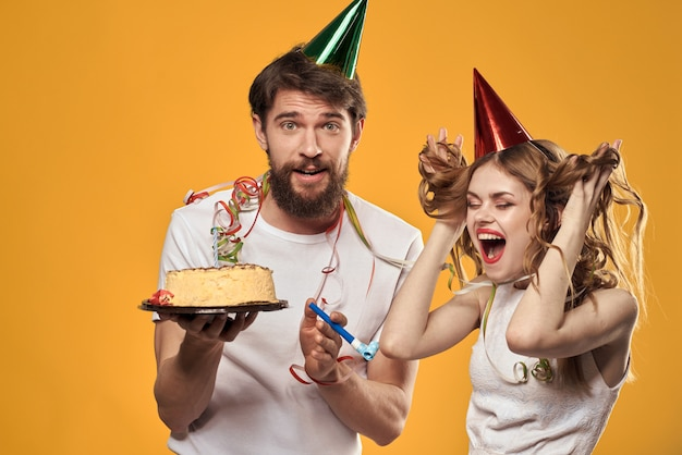 カップケーキとお祝い帽子のキャンドルで誕生日に男女が楽しんで、休日を一緒に祝う、幸せなカップル
