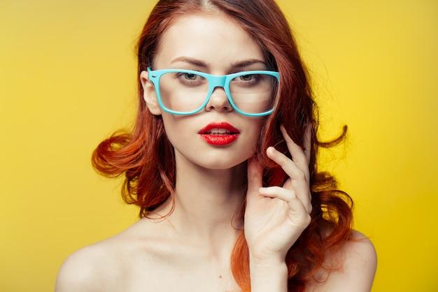 女性メガネ明るい黄色オレンジ色の壁