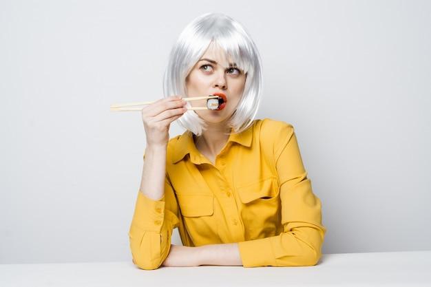 さまざまな感情のポーズをとって黄色のシャツを着たテーブルで食べ物の配達から寿司やロールを食べる美しい女性モデル