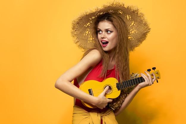 Молодая женщина с удовольствием и смех, купальник вечеринка, желтая стена играет на гитаре