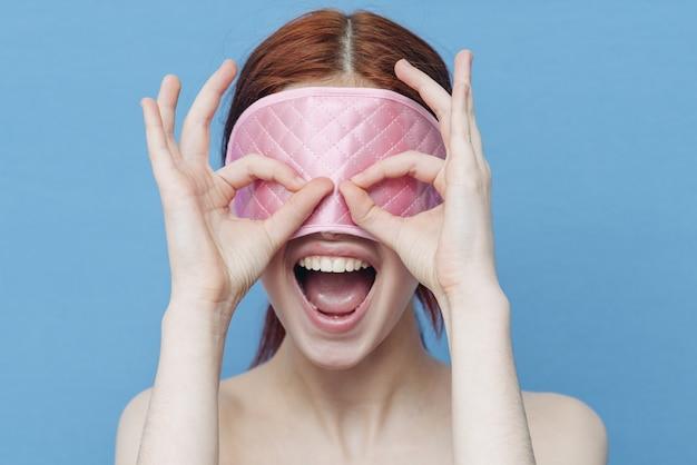 彼女の顔で寝るためのマスクを持つ女性