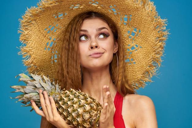 赤い水着と黄色い帽子のポーズの女性
