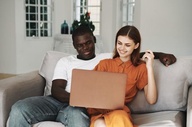 アフリカ系アメリカ人の男性と白人女性のフリーランスのラップトップ、自宅で仕事のカップル