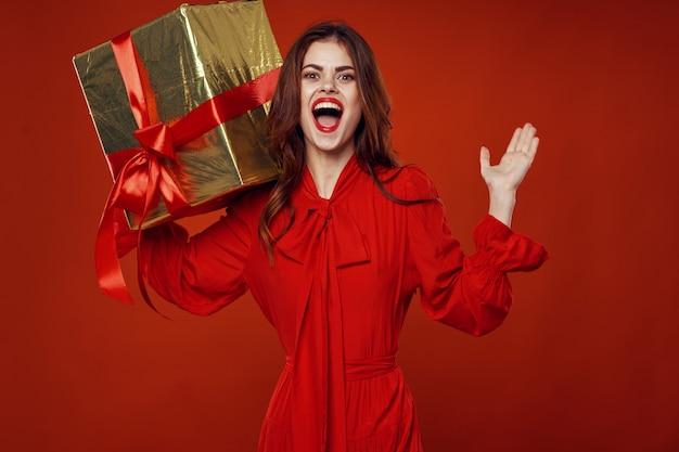 Молодая женщина с коробками подарков в руках в красивой одежде, продажа подарков, счастливого рождества и нового года
