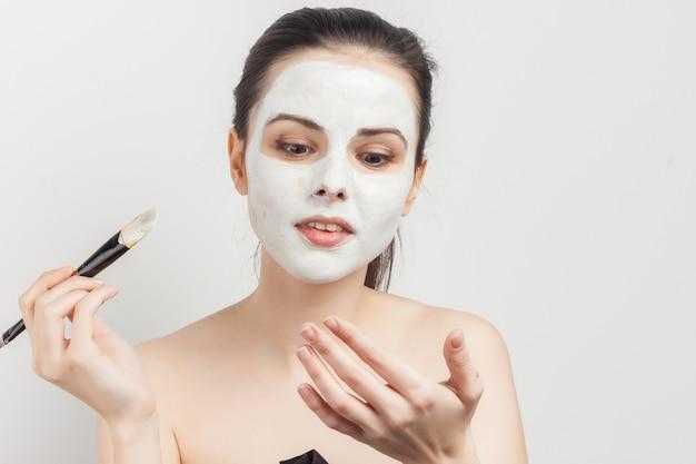 ブラシでフェイスマスクを適用する肖像若い美しい女性