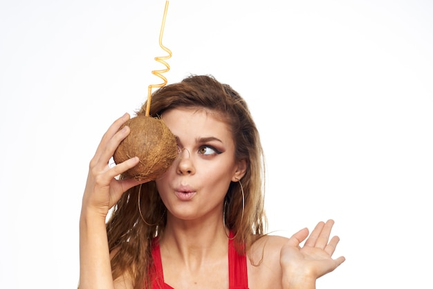 Красивая молодая женщина с вьющимися волосами в купальнике пьет коктейль из кокоса, тропики