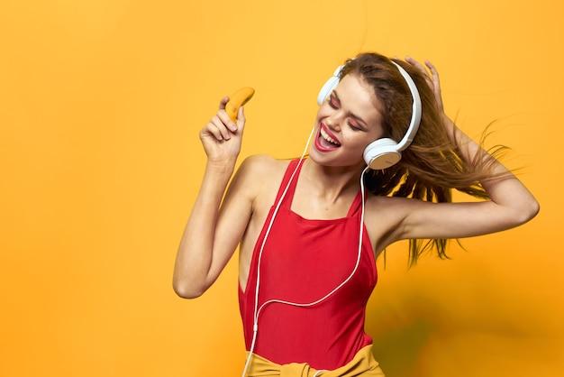 Молодая женщина в наушниках, веселье и смех, купальник, желтая стена