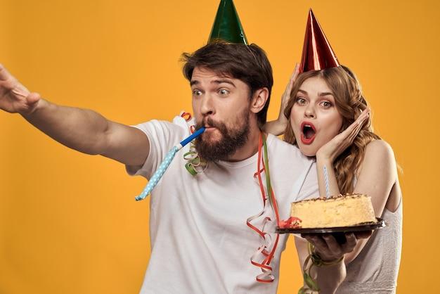 Мужчина и женщина в день рождения с кексом и свечой в праздничной кепке веселятся и празднуют вместе праздник, счастливая пара