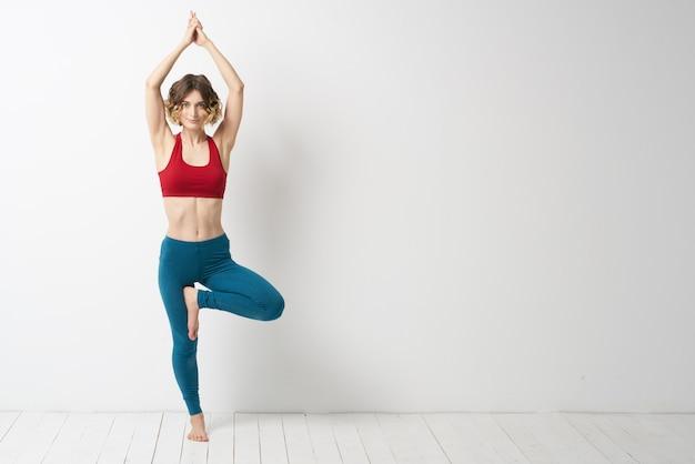 Стройная молодая женщина занимается йогой и упражнениями дома