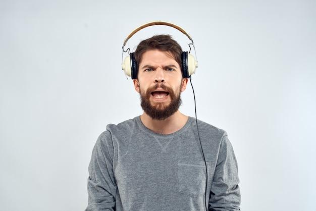 ヘッドフォンで若い男が光の壁で音楽を聴く