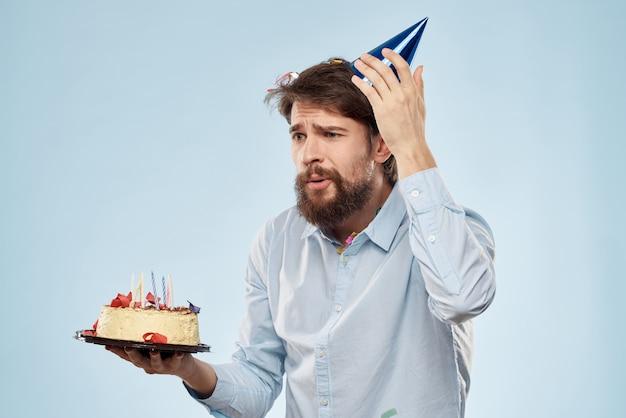 Молодой человек с праздничным тортом с кусочками празднует один день рождения в кепке