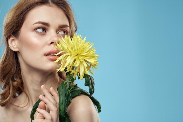 青い壁、ロマンチックな柔らかいイメージでポーズの花と美しい若い女性
