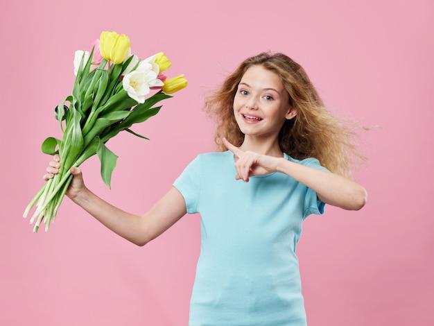 母の日、花でポーズをとる子供を持つ若い女性、女性の日と母の日への贈り物