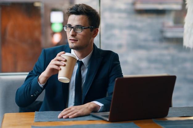 テーブルでノートパソコンとコーヒーとビジネスの男性