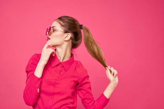ピンクの壁、面白い人形のスタイルでピンクの服の若い女性