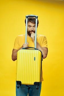 Мужской путешественник с чемоданом в руках позирует в отпуск