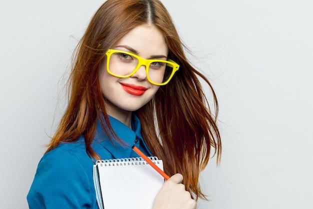 光の壁にメガネ、彼女の手でノートを持つ感情の女性モデルポーズ