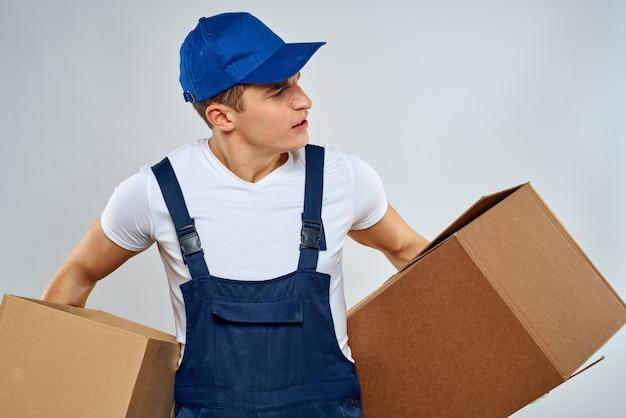 オーバーオールの若い強い男は小包、箱、商品、宅配便を提供します
