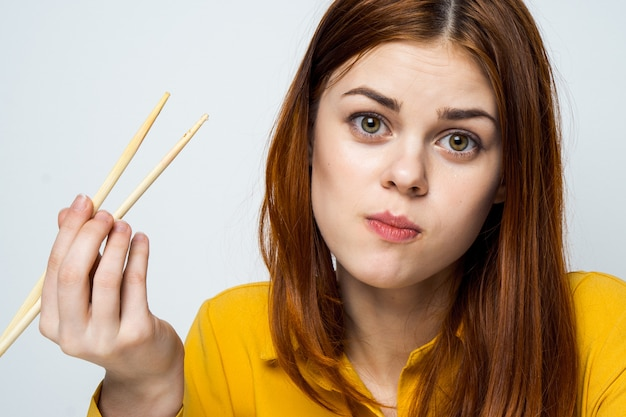 黄色のシャツのテーブルで食べ物の配達から寿司やロールを食べる美しい女性モデル