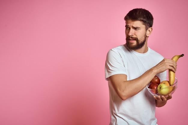 Мужчина с бородой в белой футболке с фруктами и овощами, вегетарианец