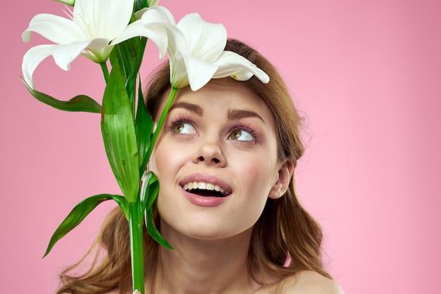 ピンクの壁、ロマンチックな柔らかいイメージでポーズ白いユリの花と美しい若い女性