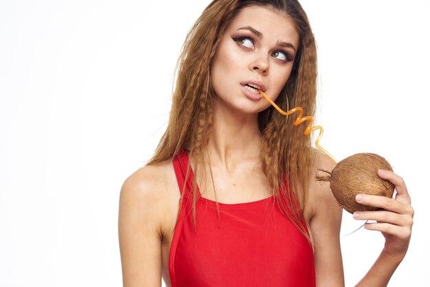水着の巻き毛を持つ美しい若い女性は、ココナッツ、熱帯からカクテルを飲む