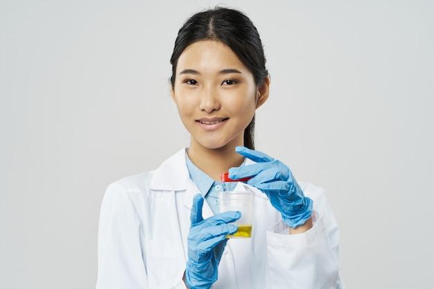 灰色の分析のための瓶を持つ医師