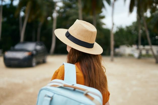 帽子とオレンジ色のシャツを着たバックパックを持つ旅行者