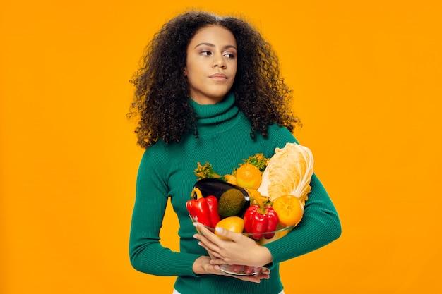 Красивая женщина в зеленой футболке и проведение овощей и фруктов