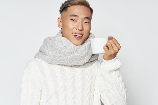白いセーターとポーズのスカーフとアジアの外観の陽気な男