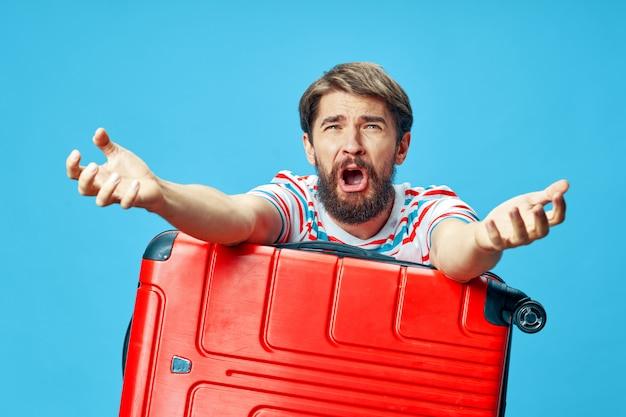 赤いスーツケースを持つ感情的な男
