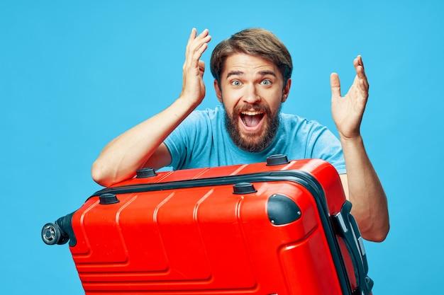休暇に赤いスーツケースと陽気な感情的なひげを生やした男