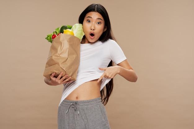 スリムな体型のベジタリアン製品パックを保持しているアジアの外観の女性