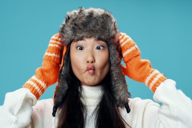 冬の帽子とオレンジの手袋を身に着けている美しい女性
