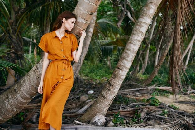 黄色のドレスと帽子を着た女性がヤシの木のある砂に沿って海に沿って歩く