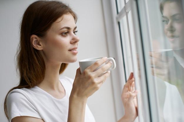 Молодая женщина отдыхает на кресле у окна дома
