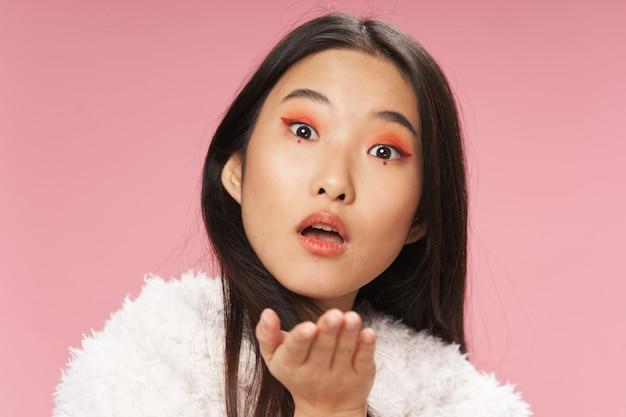 Красивая молодая азиатская женщина представляя в стильных одеждах