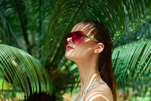 Женский портрет в очках, зеленые листья пальм, красивое лицо