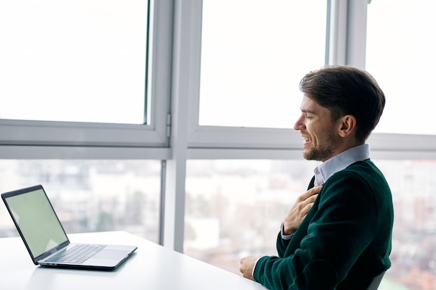 Молодой человек с ноутбуком в деловом костюме работает в офисе и дома у окна, интервью онлайн