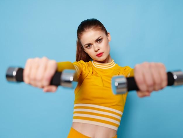 Молодая женщина в ярко-желтом спортивном костюме с гантелями занимается спортом