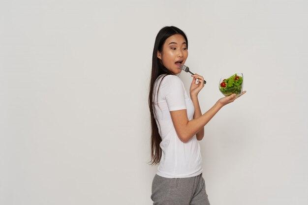 Азиатская женщина ест салат