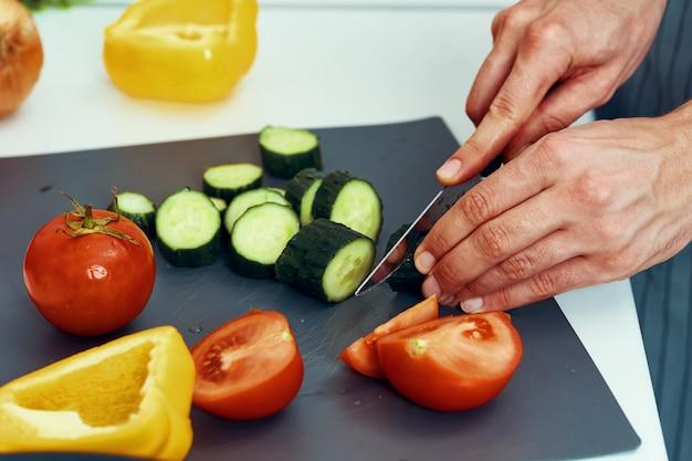 男性の料理人がキッチンで調理し、健康的な自家製料理