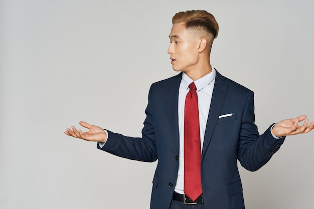 Азиатский деловой человек позирует в костюме