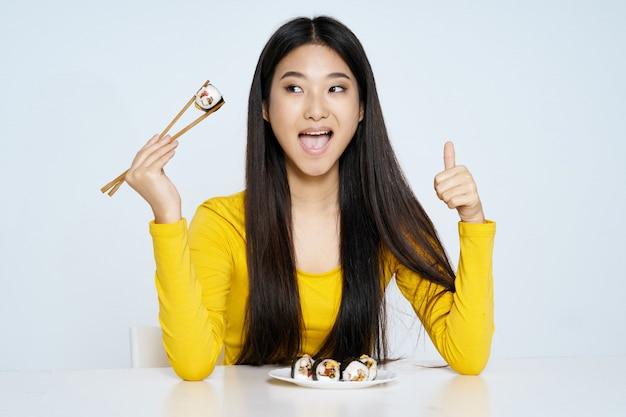 アジアの女性が食べ物の肖像画、寿司でポーズ