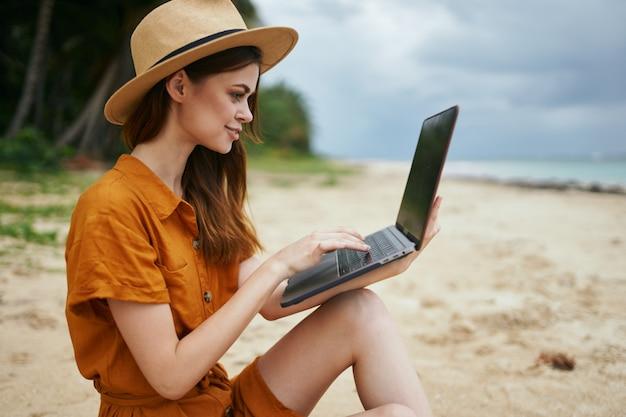 ヤシの木のある砂に沿って海に沿ってラップトップを持って旅行する女性